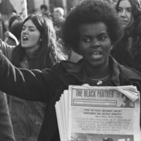 Woman holding Black Panther newspapers