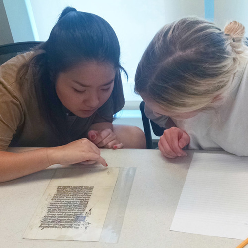 Two students take a closer look at the details in a medieval document fragment during a Hargrett Hours class session.