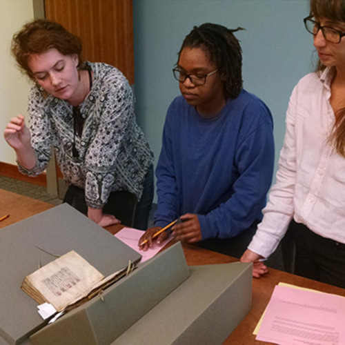 Photograph, UGA students looking at medieval manuscripts during a Hargrett Hours class session.